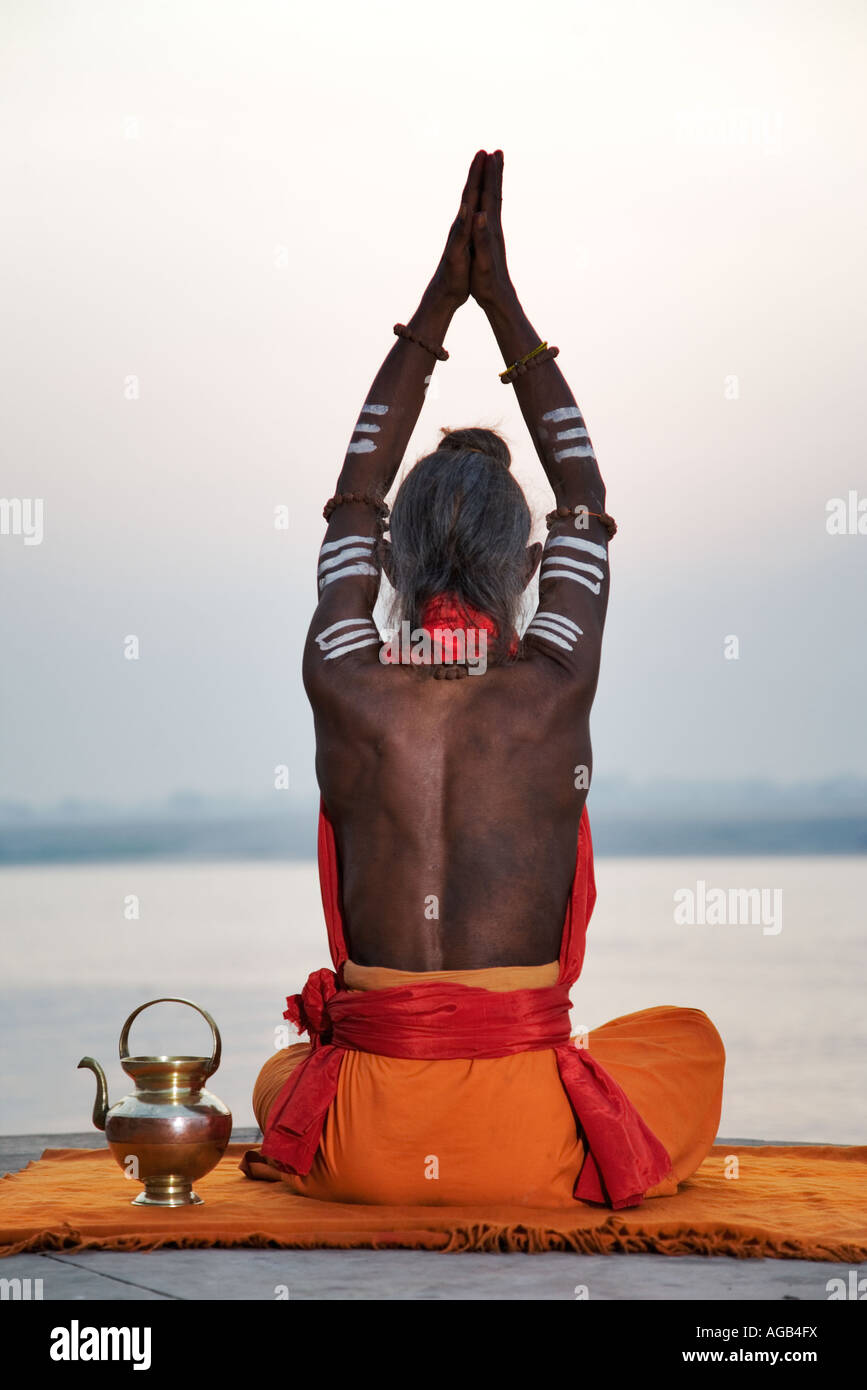 Sadhu o santo hombre realizar manas puja Río Ganges Varanasi India Foto de stock
