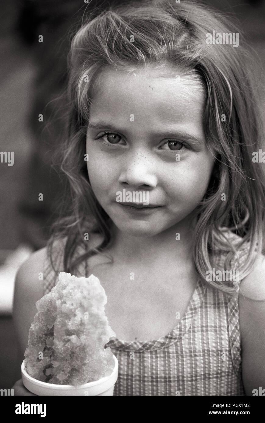 Chica sujetando un cono de nieve en un día de verano. Foto de stock