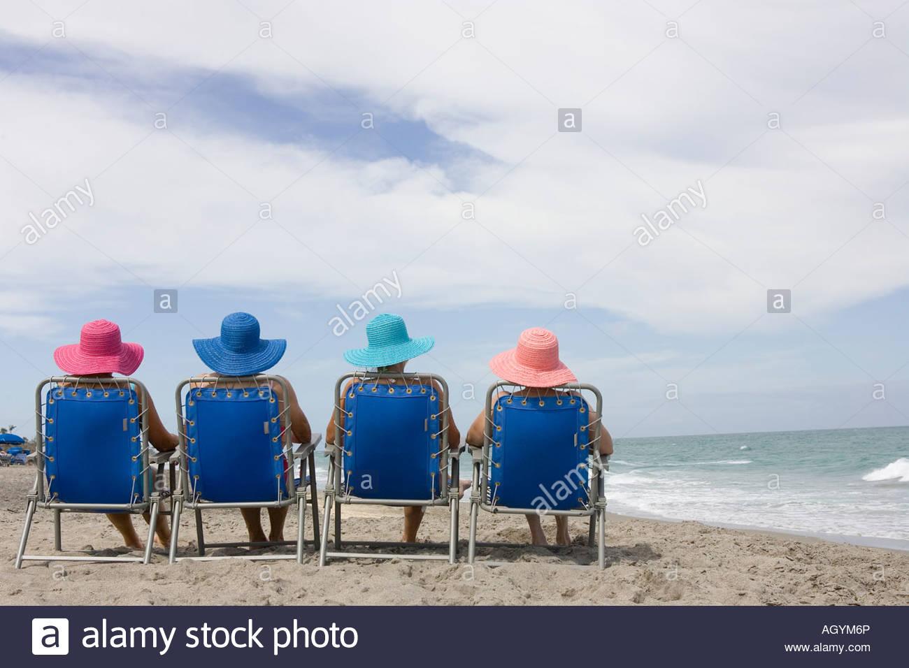 Vista Trasera De Cuatro Mujeres En Sillas De Playa Foto