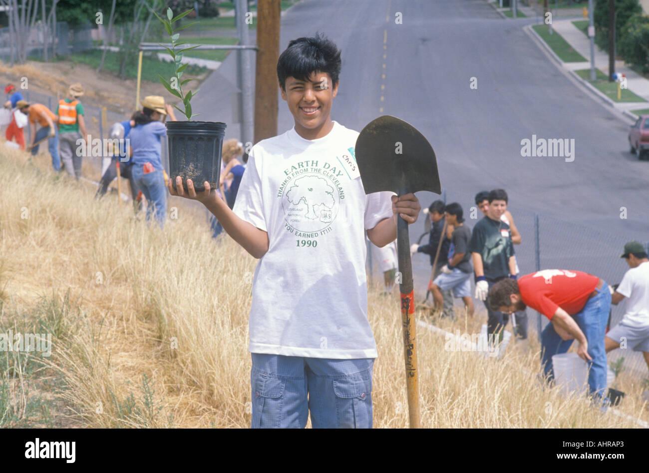 Un muchacho luciendo una camiseta del día de la tierra que participan en una plantación de árboles por los voluntarios verde limpio de Los Angeles Imagen De Stock