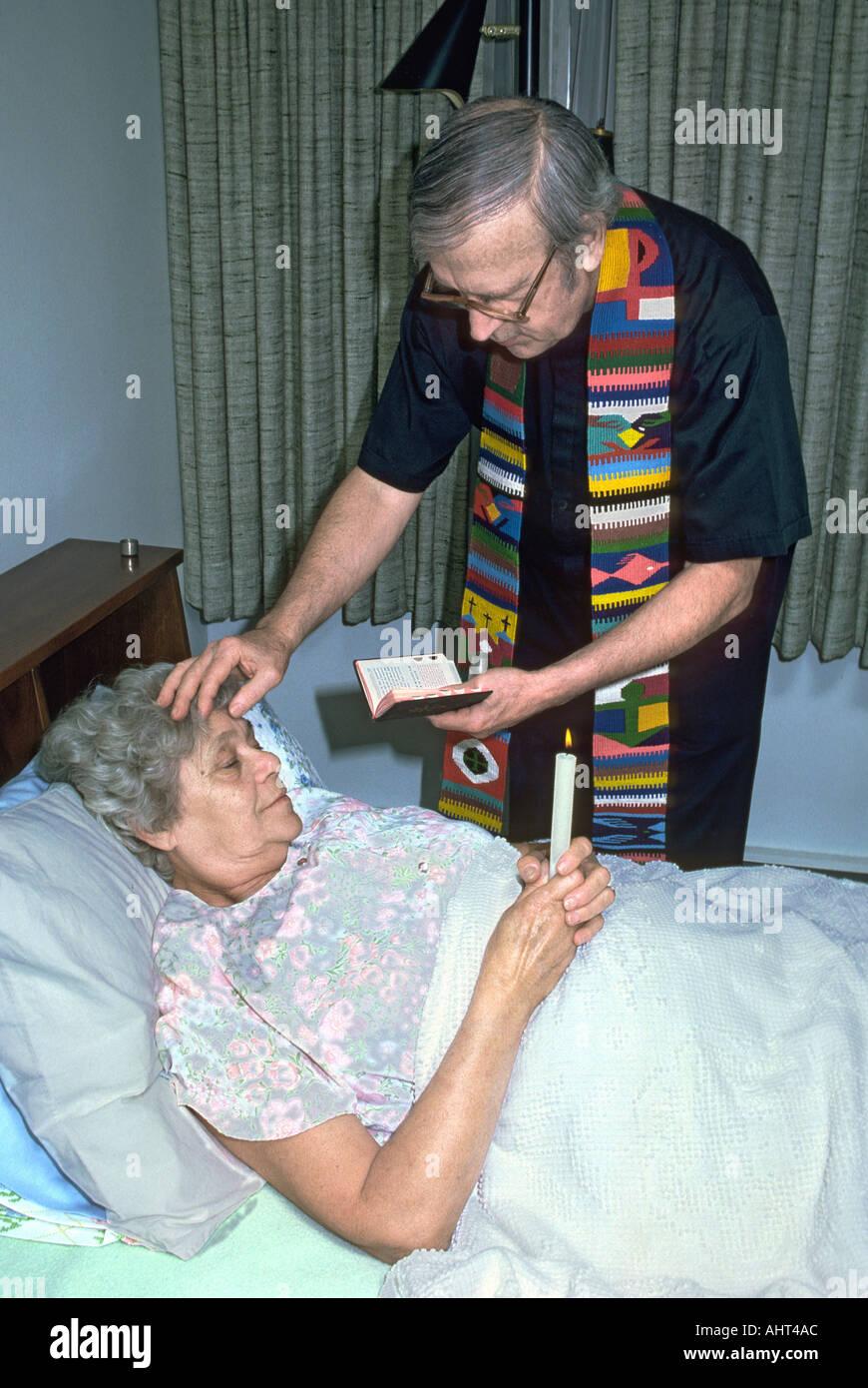 El sacerdote católico administra la extremaunción a mayores femenino senior Foto de stock
