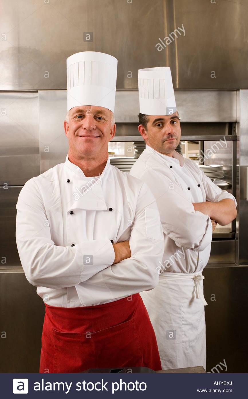 Dos chefs masculinos de pie en cocina comercial brazos cruzados retrato sonriente Imagen De Stock