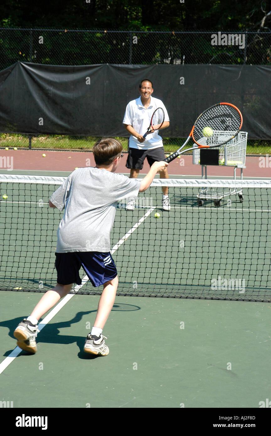 Los niños aprenden a jugar al tenis en la Recreación Pública corte Imagen De Stock