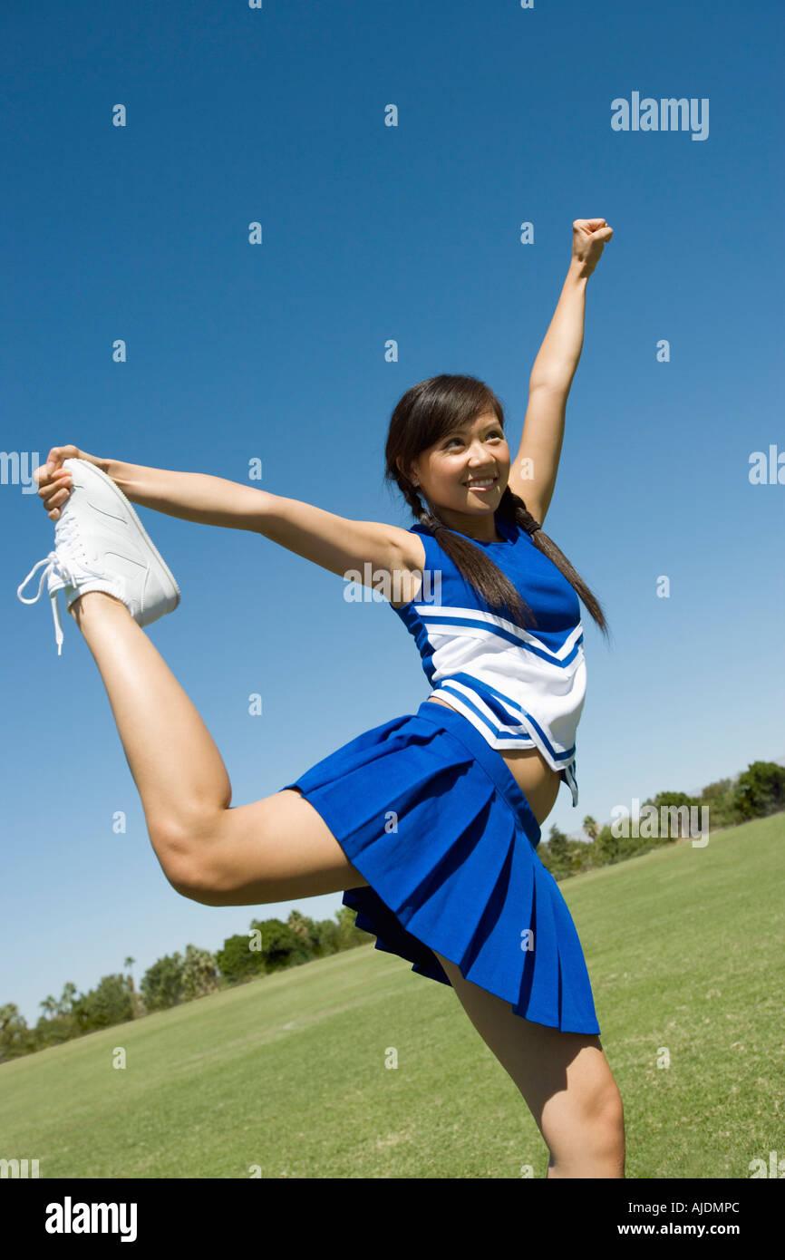 Animadora adolescente estirando sobre el césped Imagen De Stock