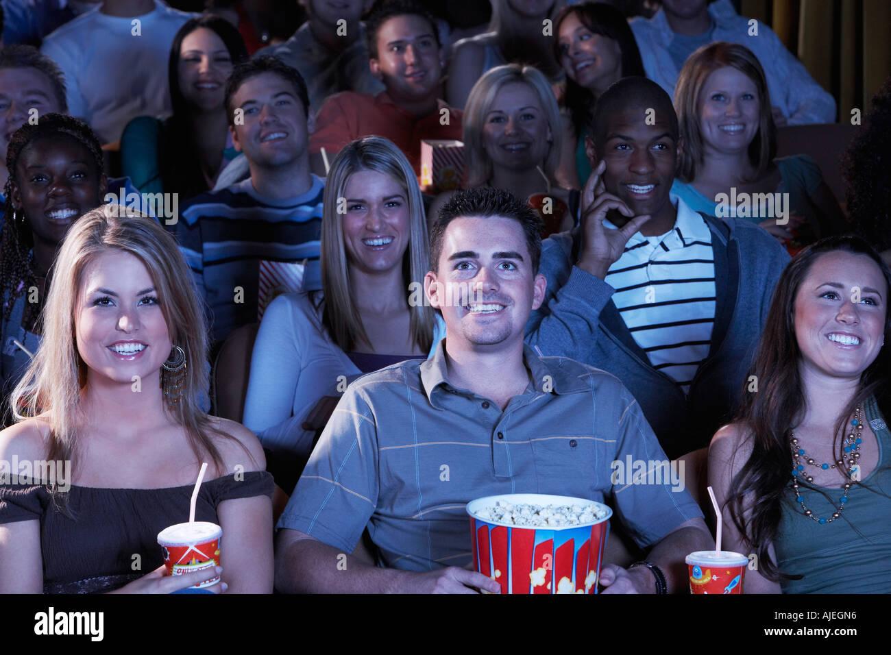 Personas sosteniendo soda y palomitas de maíz, viendo la película en el teatro Imagen De Stock