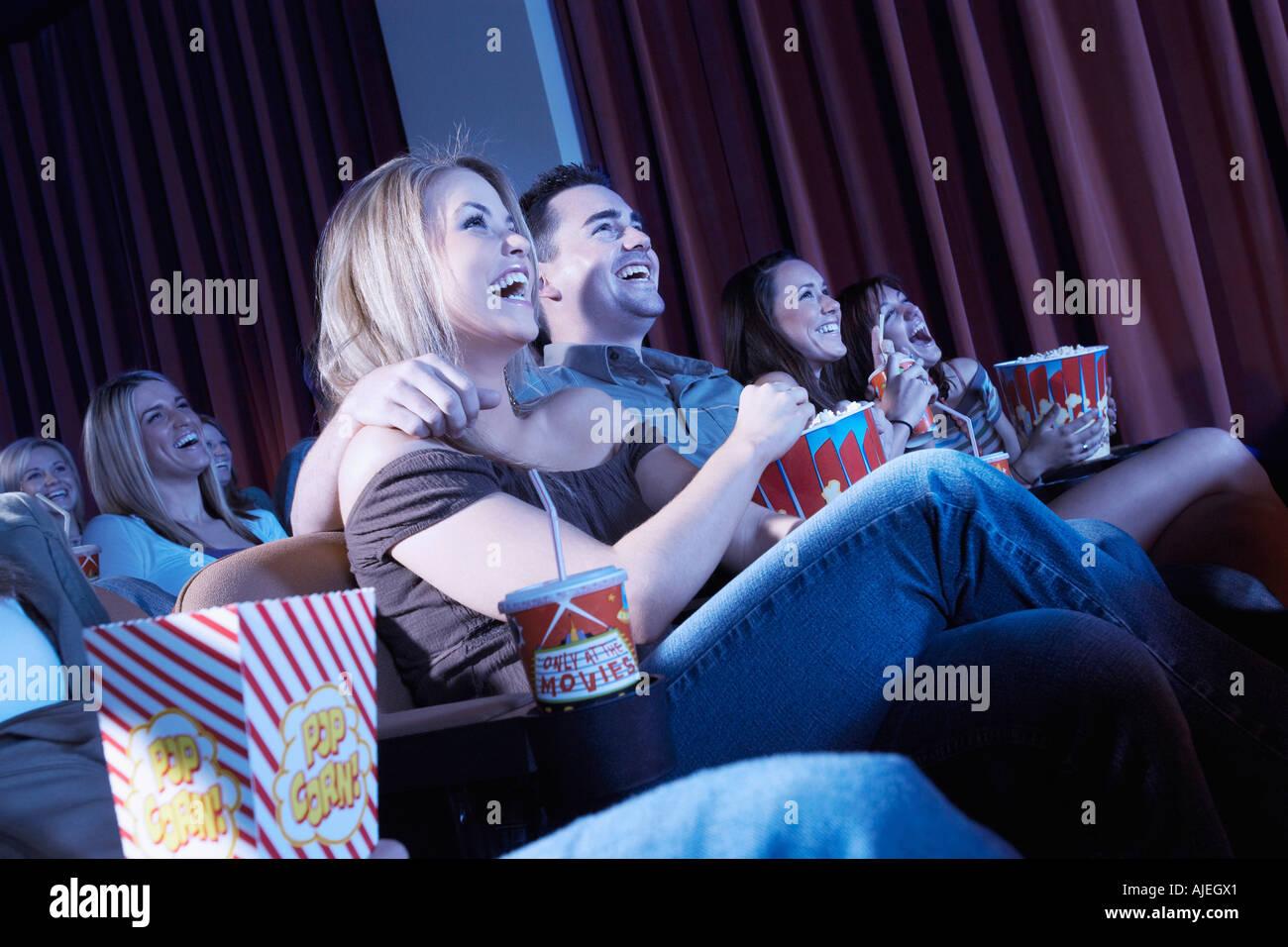 Pareja sonriente sentado, los brazos alrededor, viendo la película en el teatro Imagen De Stock