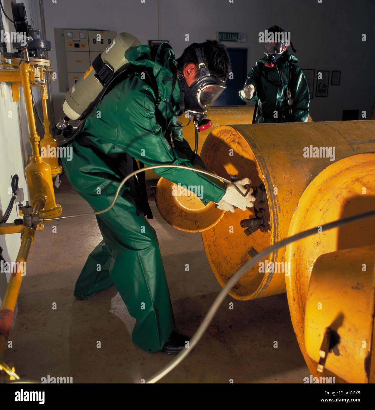 Los operadores cambiar tanques de cloro para uso en la planta de tratamiento de agua, de Tawau, Sabah, Malasia Foto de stock