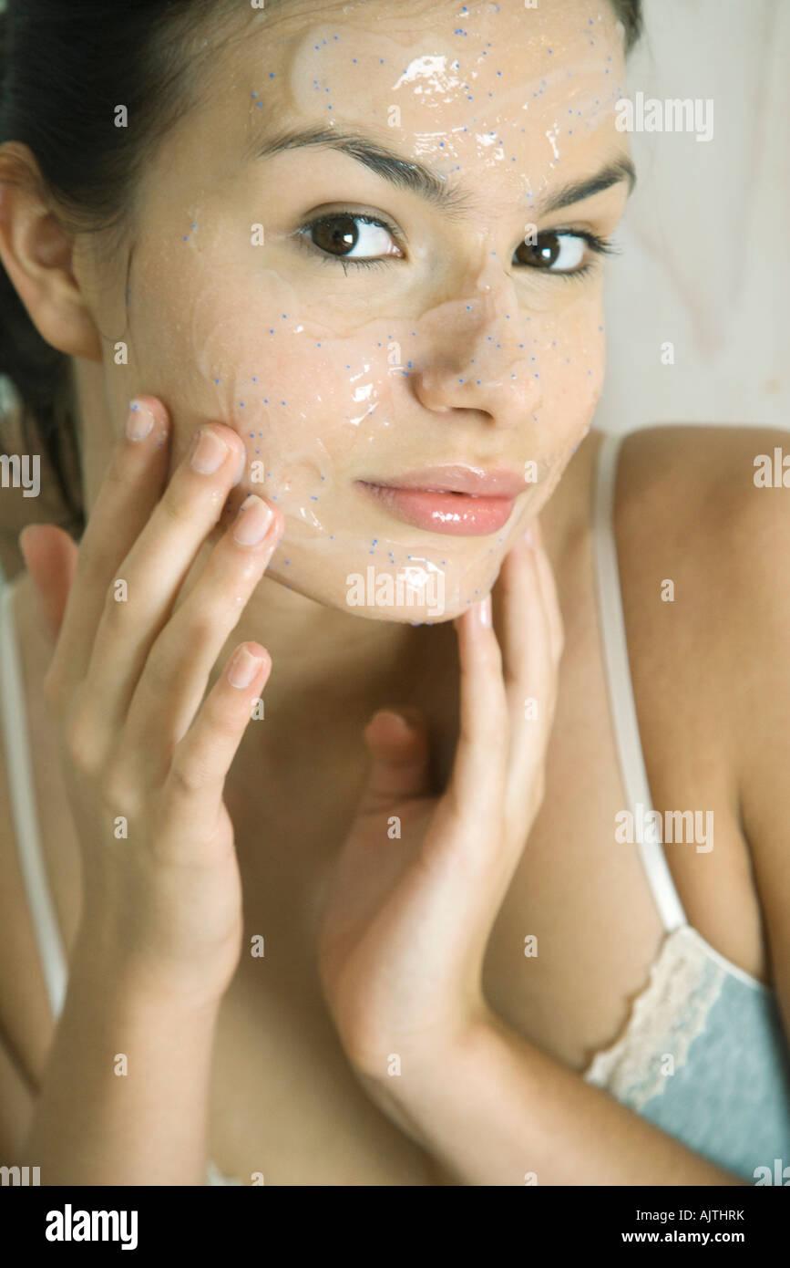 Mujer joven poniendo máscara exfoliante en la cara, sonriendo a la cámara Imagen De Stock
