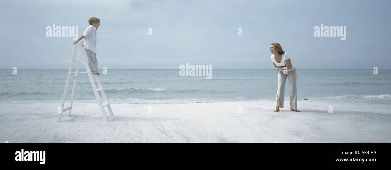 Niño de pie en la escalerilla en la playa mirando a la madre Imagen De Stock