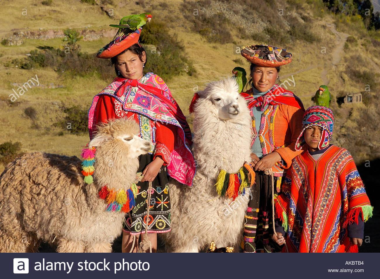 Las mujeres con niños en vestimentas nativas y sombrero sujetando Llamas Perú Imagen De Stock