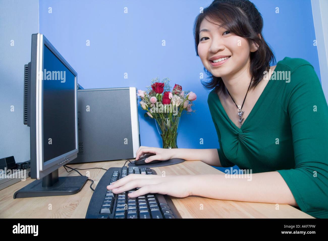 El perfil lateral de una joven mujer utilizando un ordenador y sonriente Foto de stock