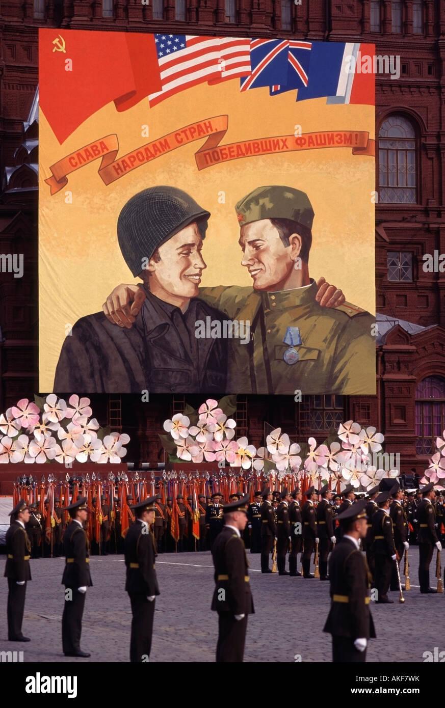 Los soldados rusos en la Plaza Roja bajo un póster celebrando el final de la II Guerra Mundial, Moscú, Rusia Foto de stock