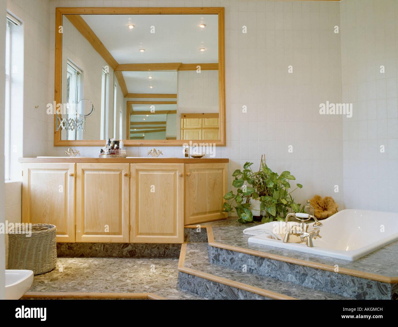Gran espejo sobre la madera pálida tocador en el baño, con escalones ...
