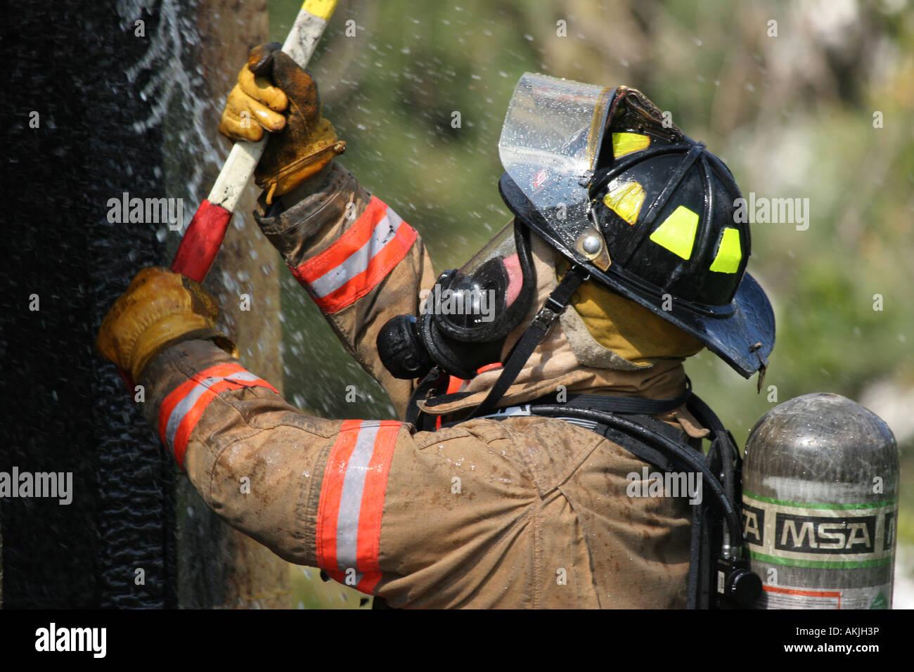 Un bombero con un hacha en una estructura de fuego ser rociado con agua sobre el fuego Imagen De Stock