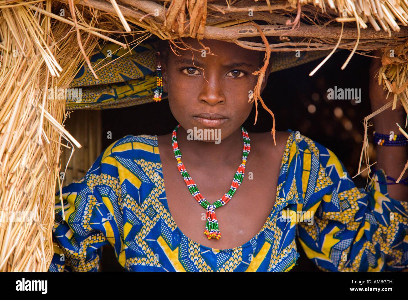 Niña de África occidental enmarcada por la puerta de una casa de ...
