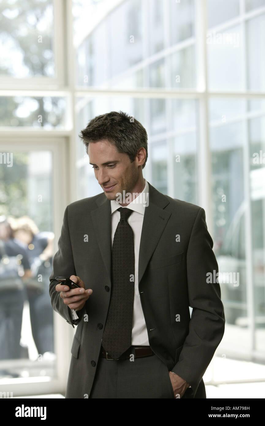 Hombre de negocios con un teléfono móvil en el vestíbulo Foto de stock