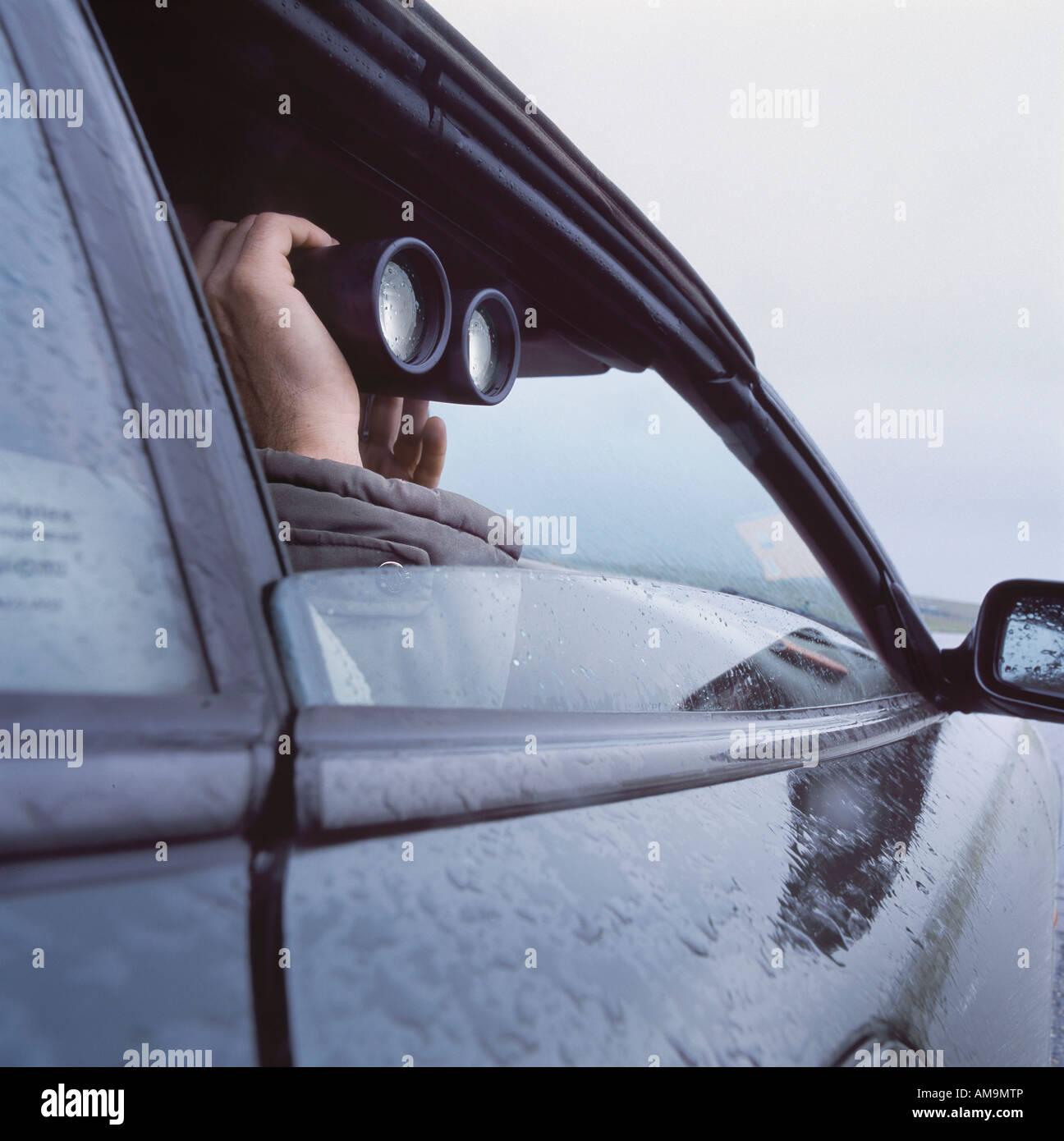 Hombre con prismáticos peeking a través de ventanilla. Imagen De Stock