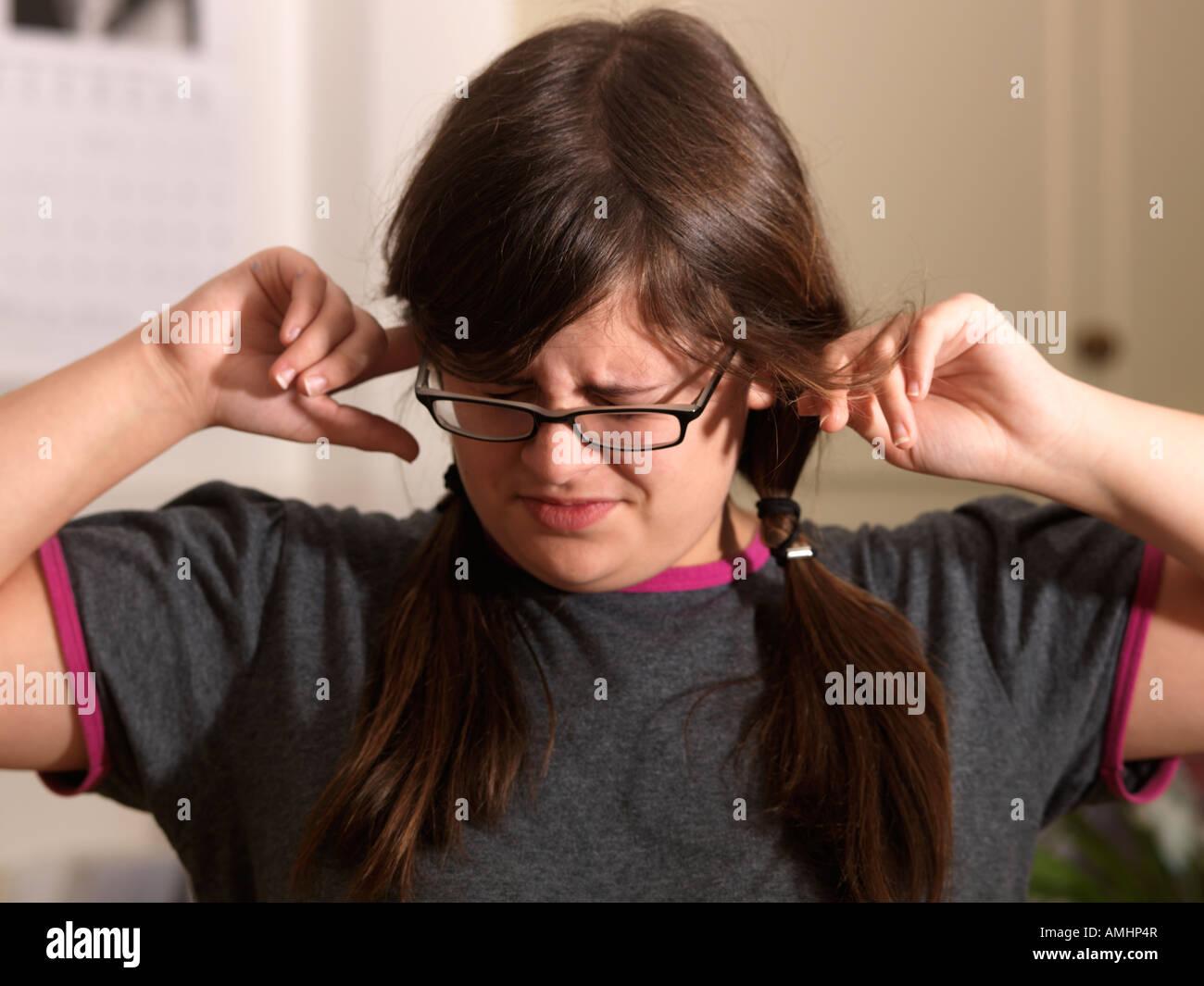 Adolescente con los dedos en las orejas. Imagen De Stock