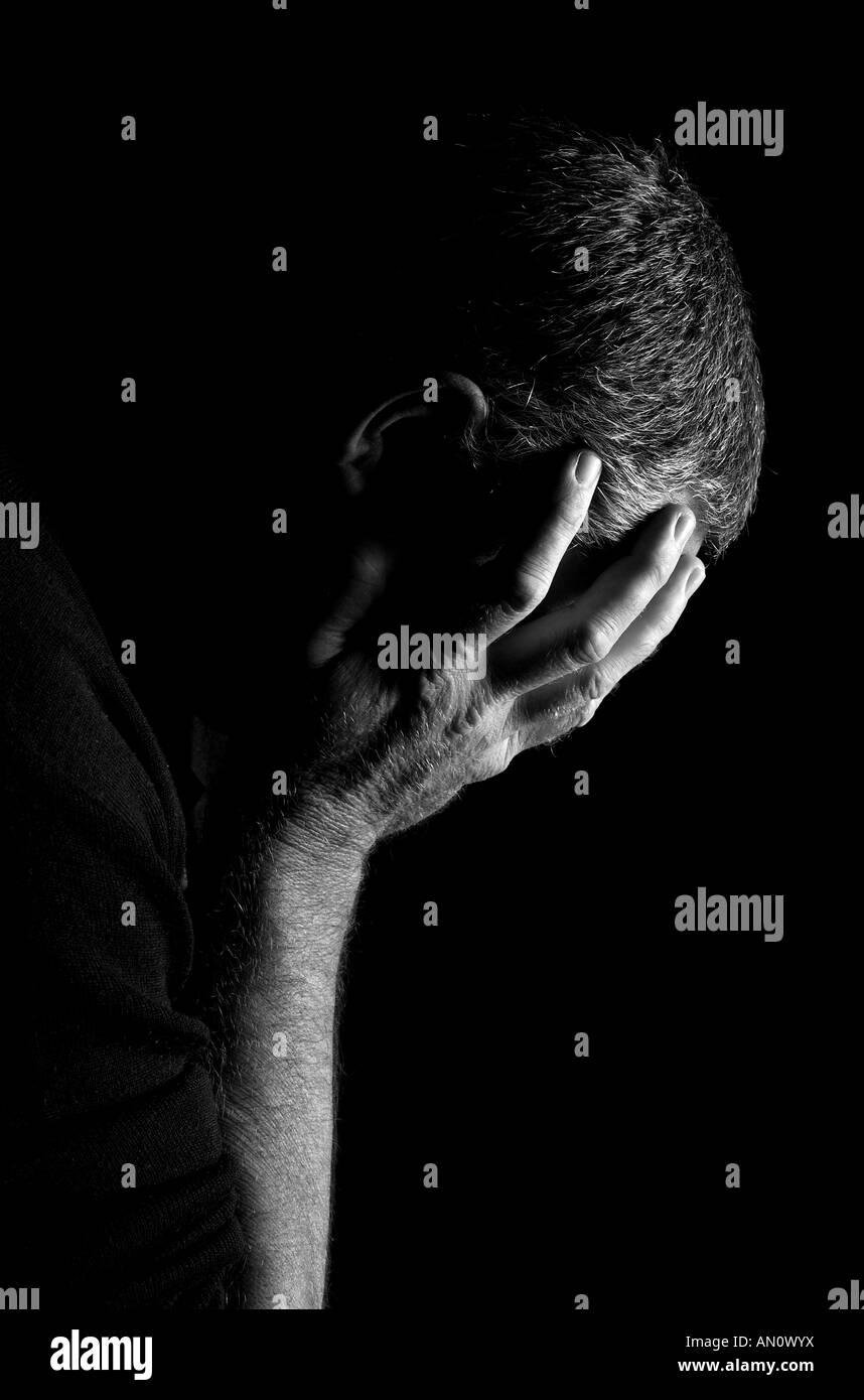 Una foto de perfil de un hombre abatido, la cabeza entre las manos. Imagen De Stock