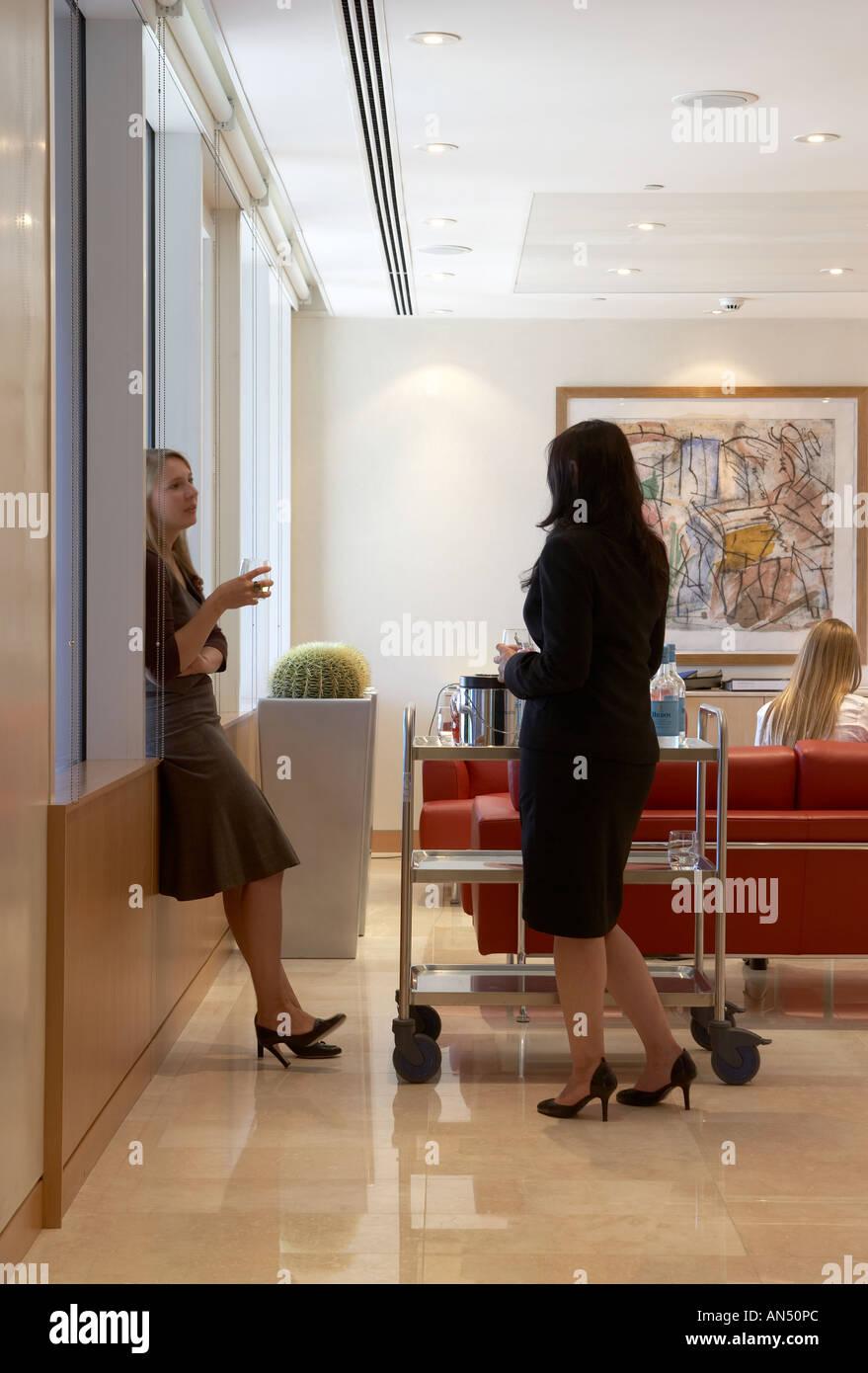 Vida de oficina e interiores de la segunda parte. Los empleados en la sala de personal hablando. Imagen De Stock