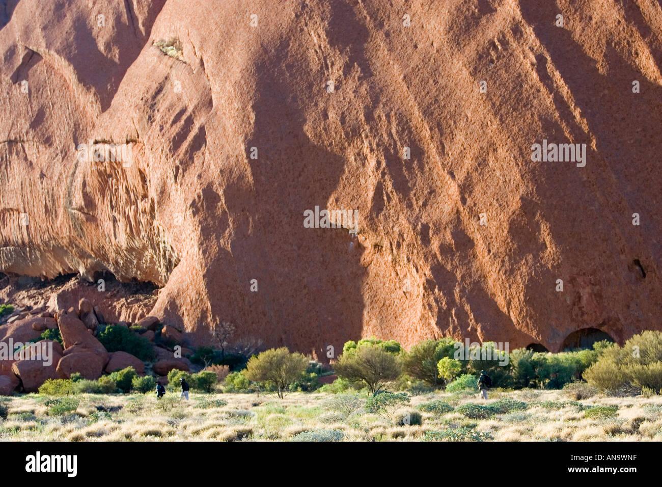 Los turistas en la base del Uluru Ayers Rock Australia Foto de stock