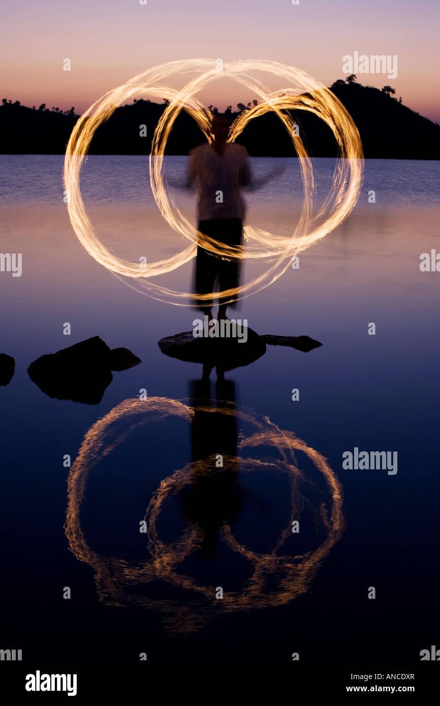 Hombre de fuego bailando sobre una roca en un lago en la India Imagen De Stock