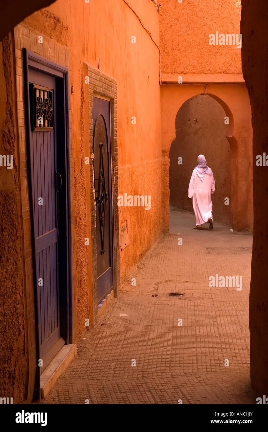 Mujer musulmana en blanco jellabas caminando en el misterioso rojo medina de Marrakech - Marruecos. Imagen De Stock