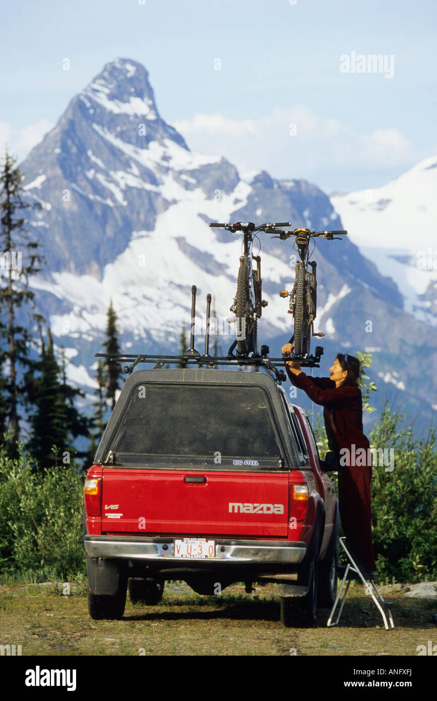 Una joven mujer teniendo una bicicleta de montaña de la roofrack de un camión, justo antes de aventurarse Imagen De Stock