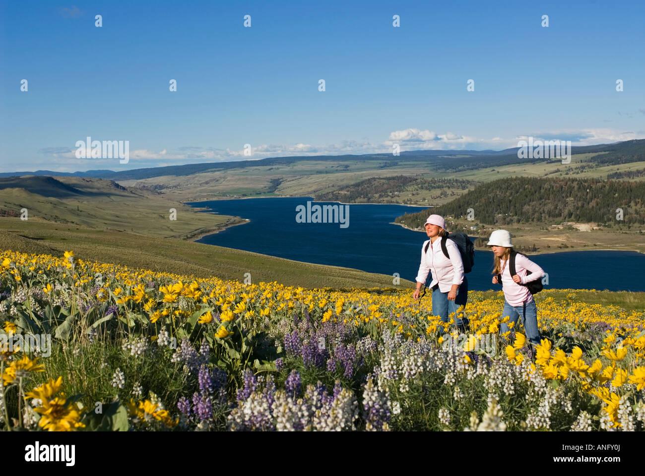 Una niña y su madre disfrute de un hermoso día de primavera entre las flores silvestres a través Imagen De Stock