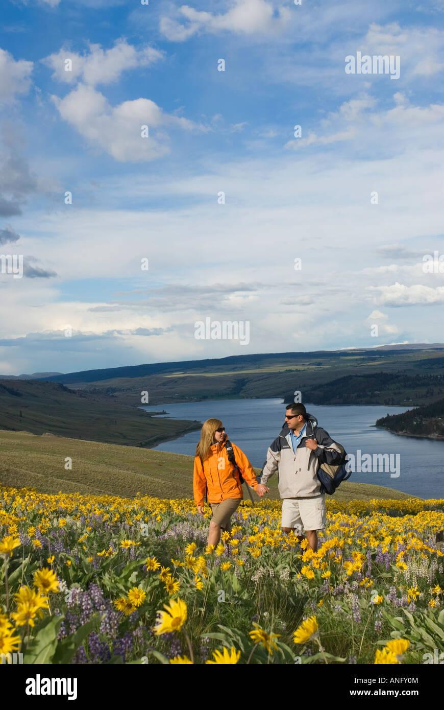 Una joven pareja disfruta de un romántico paseo a través de flores silvestres en plena floración Imagen De Stock