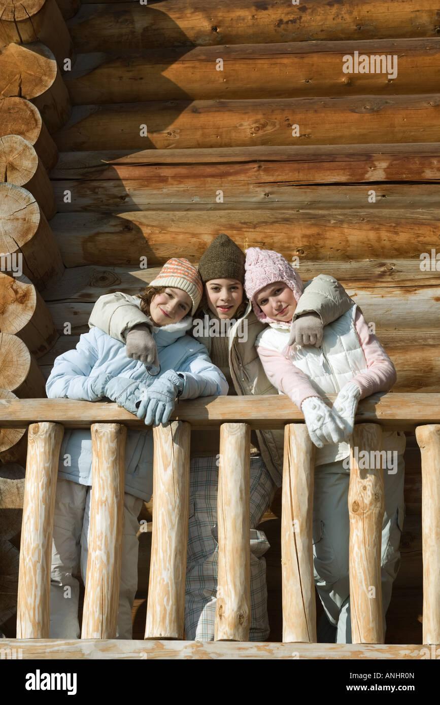 Tres preadolescentes o adolescentes de pie en la cubierta de la cabaña, sonriendo a la cámara Imagen De Stock
