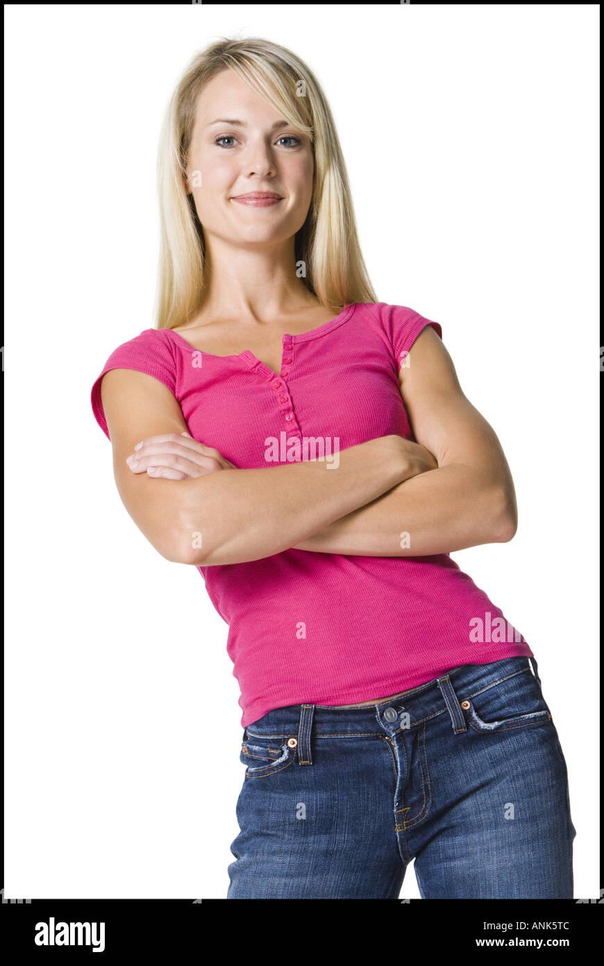 Retrato de una joven mujer de pie con los brazos plegados Foto de stock