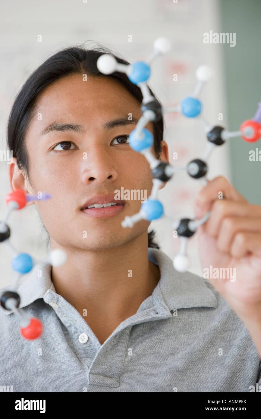 Estudiante universitario masculino asiático mirando modelo de molécula Foto de stock
