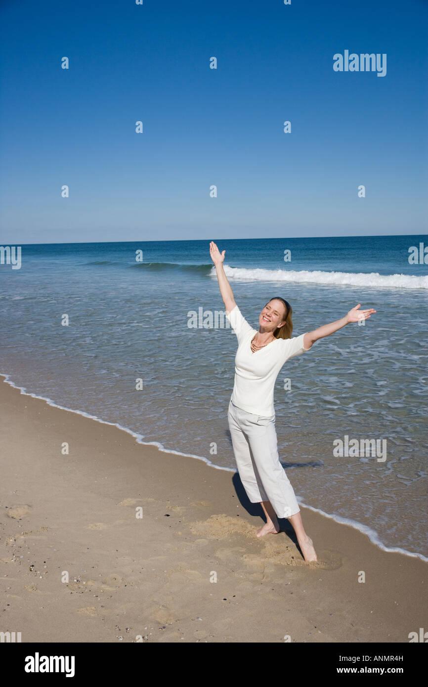 Mujer con los brazos levantados en la playa Imagen De Stock