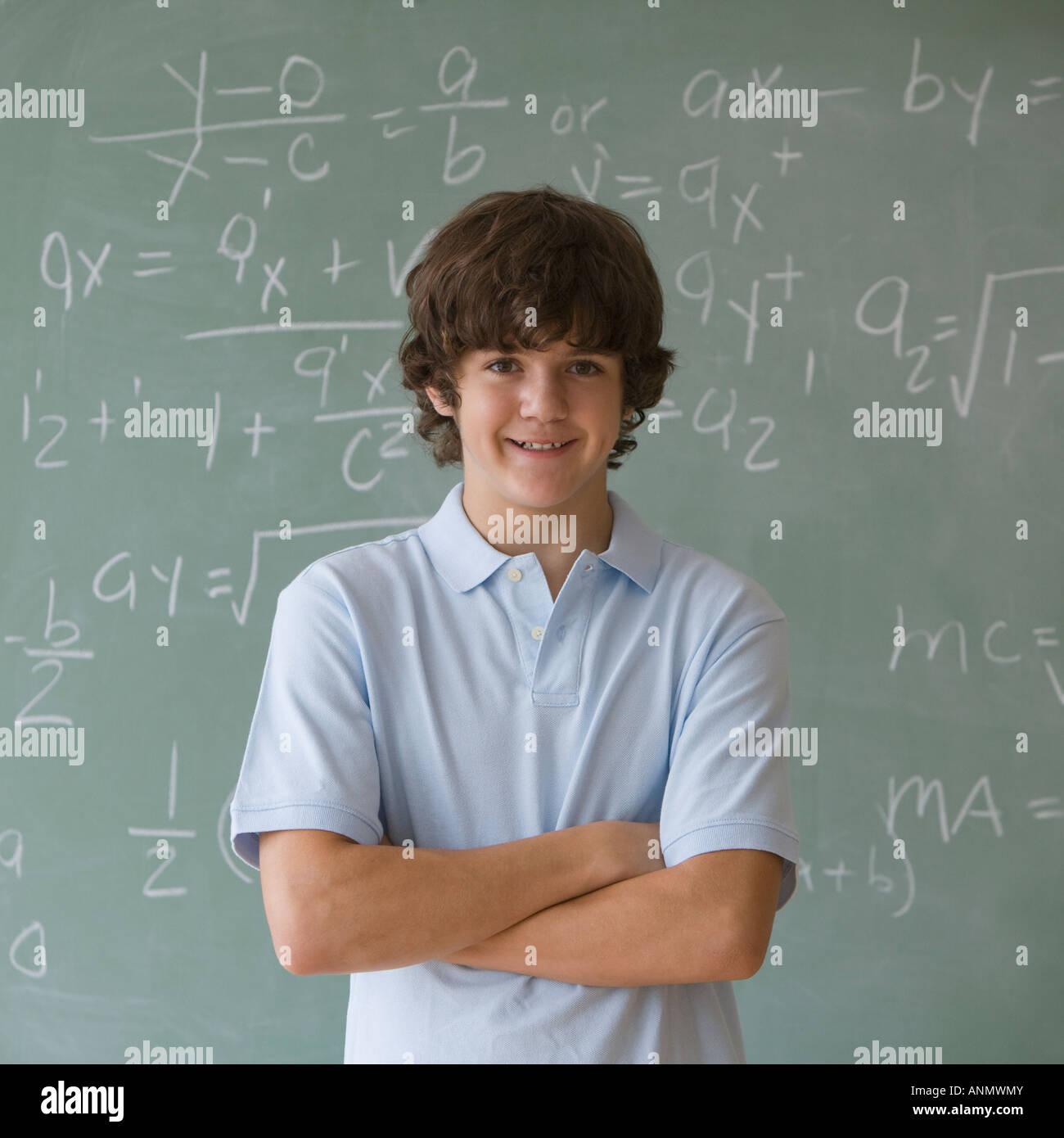 Muchacho adolescente delante de pizarra con ecuaciones matemáticas Imagen De Stock