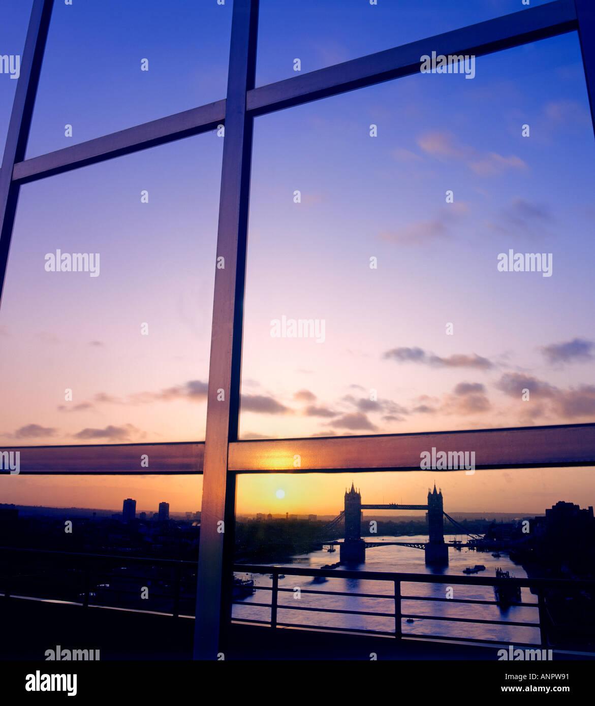 El río Támesis y el Puente de la torre se refleja en la ciudad moderna edificio de oficinas financieras ventanales en Sunrise, Londres, Gran Bretaña. Imagen De Stock