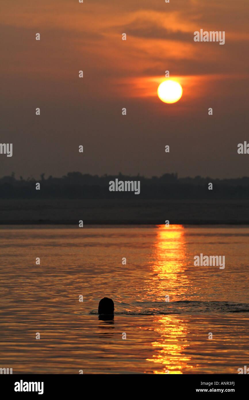 El hombre nadar al amanecer en el río Ganges en Varanasi, India Imagen De Stock