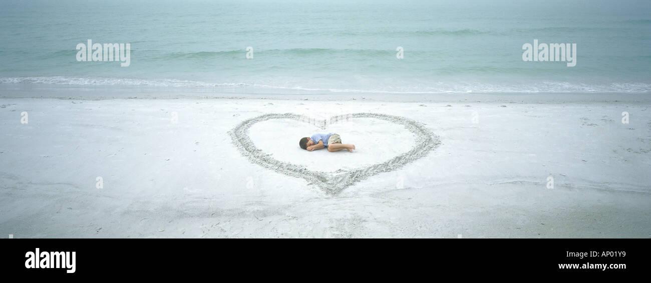 Niño que yace dentro del corazón dibujado en la playa Foto de stock