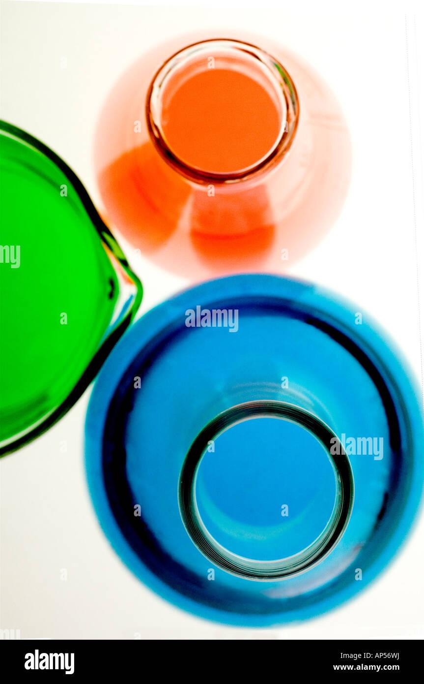 Matraces de laboratorio y vaso con líquidos de colores. Imagen De Stock