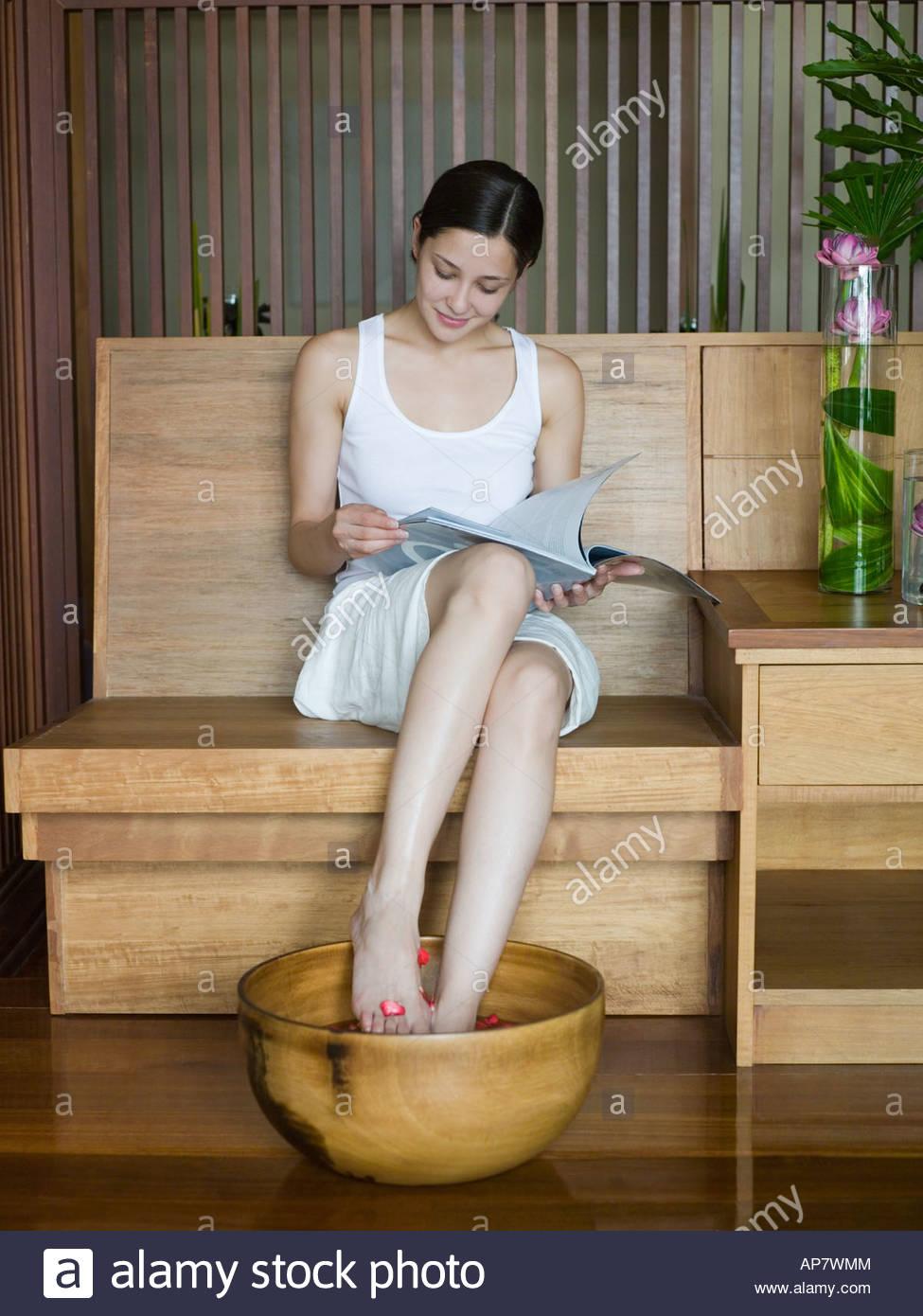 Mujer joven con un remojo de pies Imagen De Stock