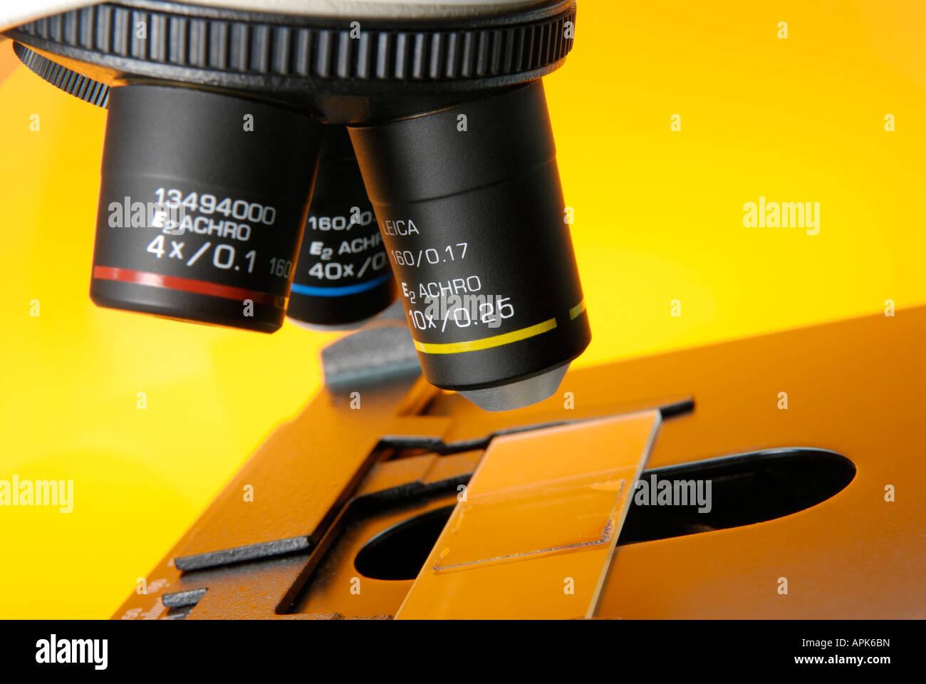 Cerca de un microscopio en un laboratorio de investigación que muestra la lente del objetivo y una diapositiva Imagen De Stock