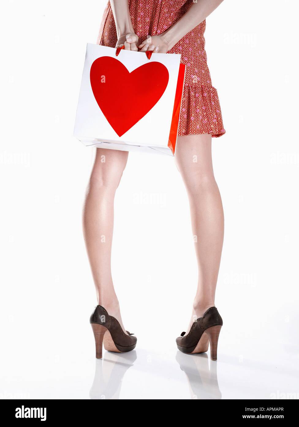 Mujer joven en vestido rojo celebración shopping bag detrás de su espalda (bajo la sección, vista trasera) Foto de stock
