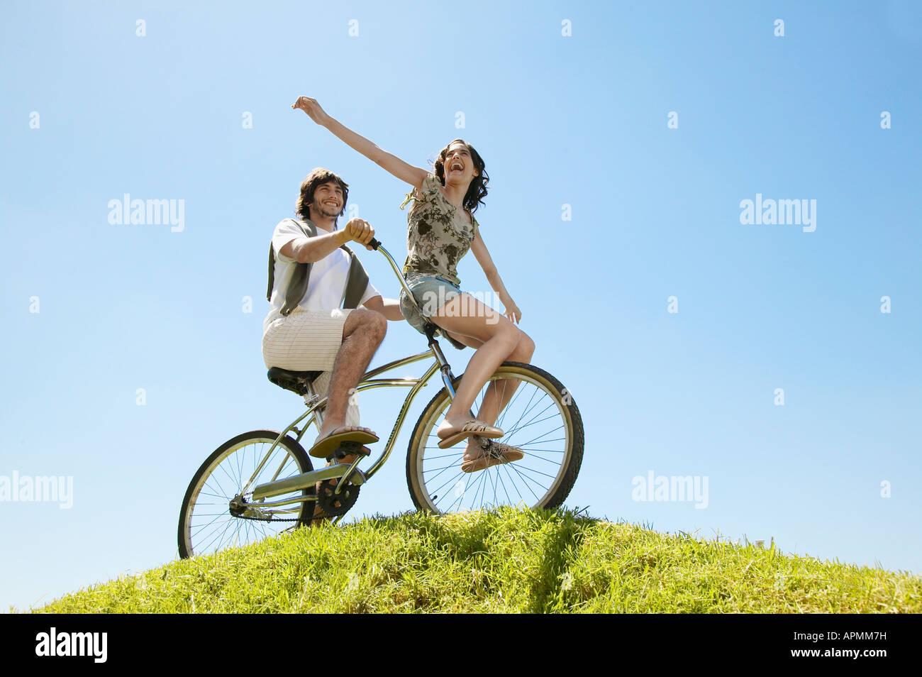 Pareja joven en bicicleta por Hill (ángulo de visión baja) Foto de stock