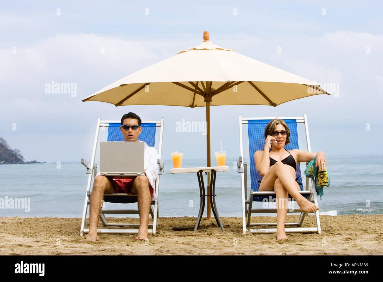 Pareja utilizando el portátil y teléfono en la playa Foto de stock
