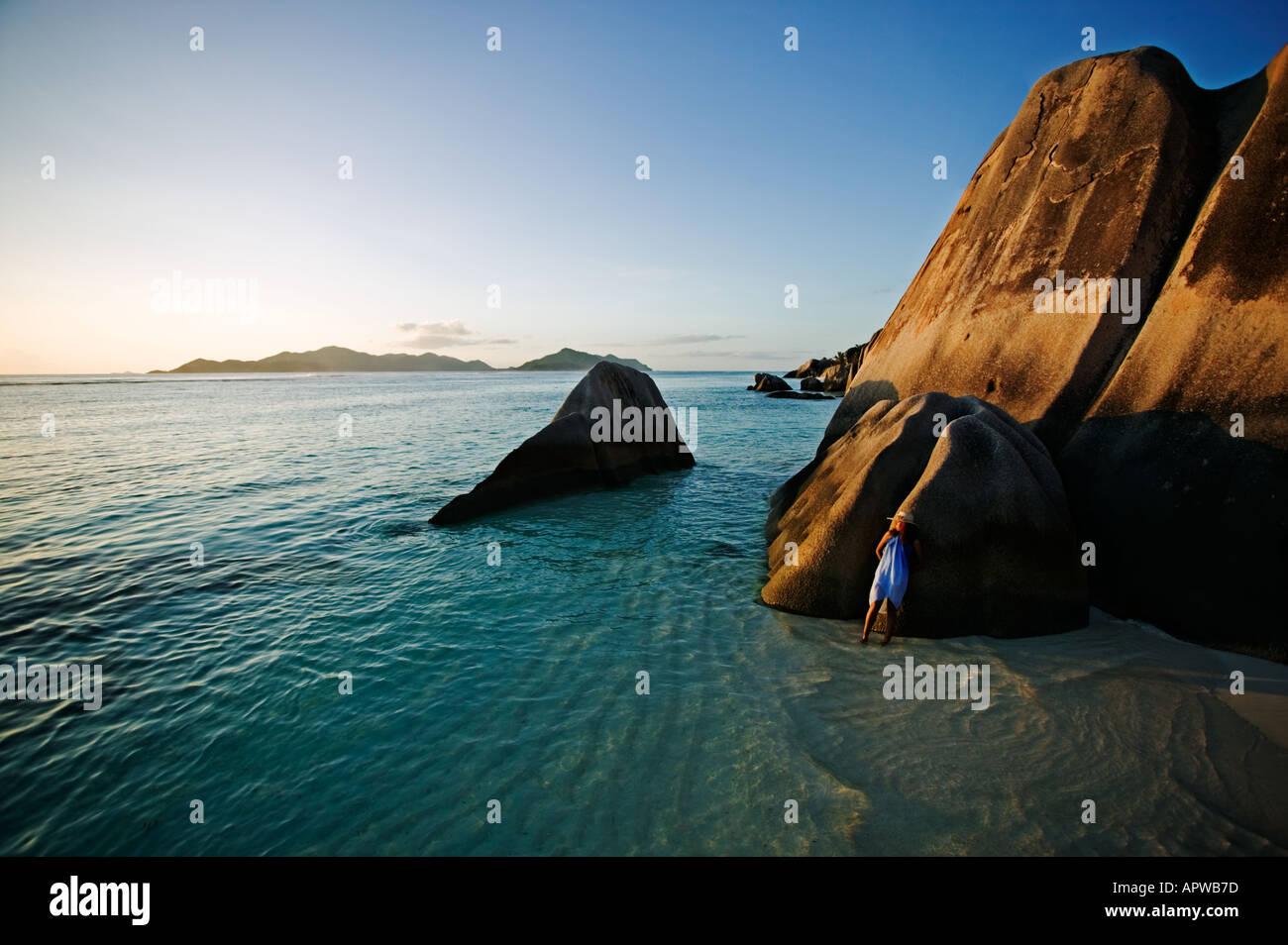 Mujer relajante sobre rocas de granito de playa modelo liberado Anse Source D Argent Playa Isla de La Digue Seychelles Imagen De Stock
