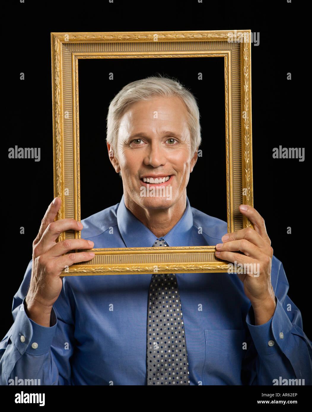 Empresario de mediana edad caucásico sonriendo a través del marco de ...