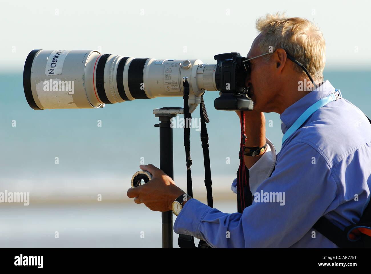 Un fotógrafo con una cámara réflex digital con un gran lente de zoom telescópico, fijada en un trípode Foto de stock
