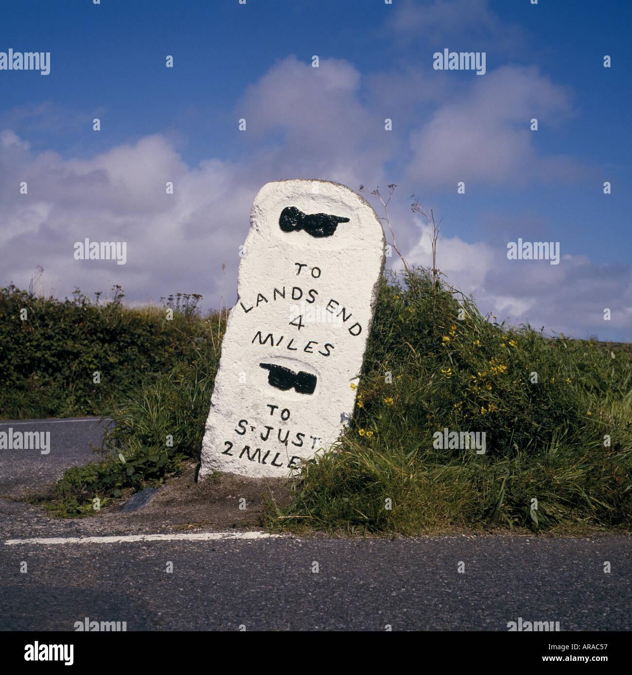 Un hito de piedra a la vera del camino en Penwith Cornwall indicando la distancia de Lands End y San Justo Foto de stock