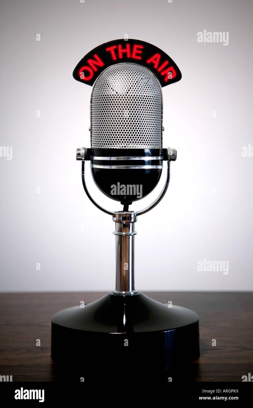 Micrófono retro con una señal luminosa en el aire sobre un escritorio vignetted antecedentes Foto de stock