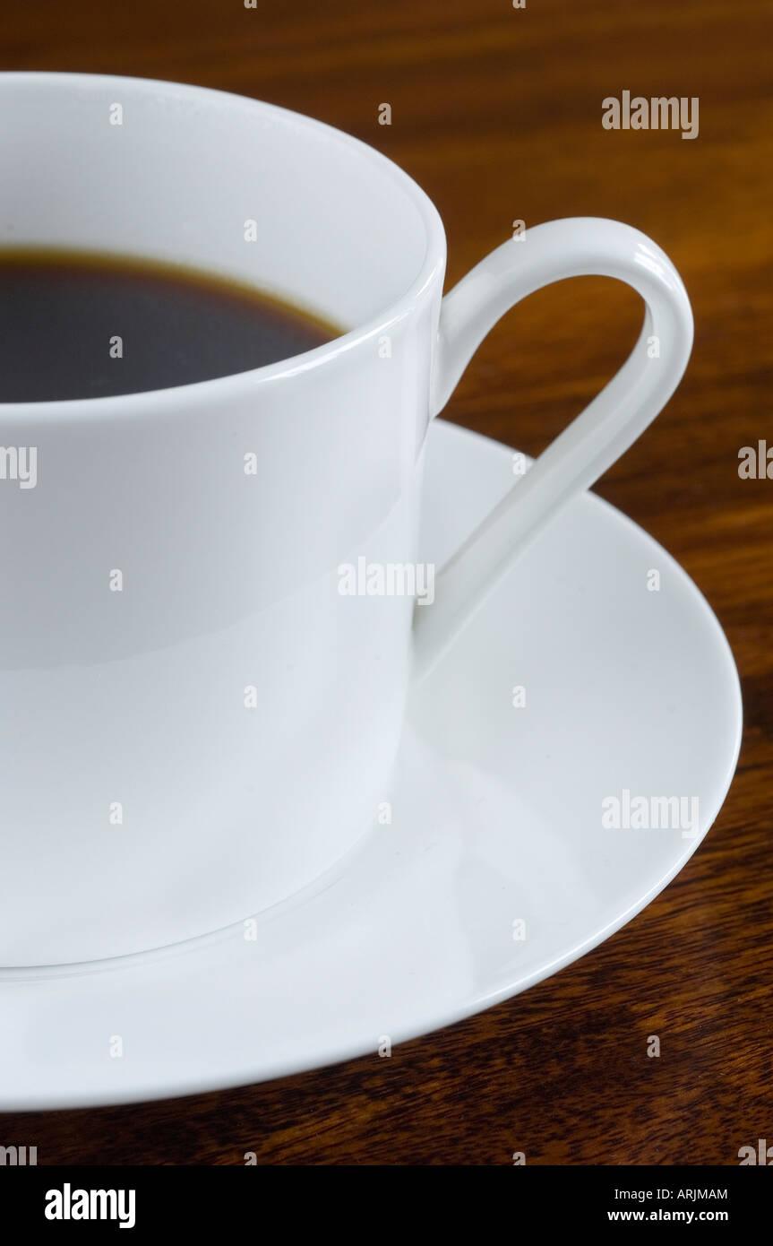 Porcelana de una taza de café recién hecho y vierte café en un platillo blanco estaba de pie en una Imagen De Stock